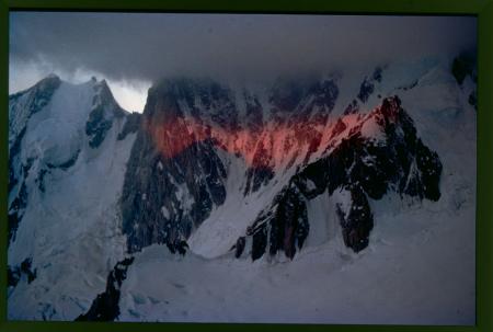 [Monte Bianco: all'alba, filtrando tra la cortina delle nubi, un raggio illumina la parete della Brenva, 1975 circa]