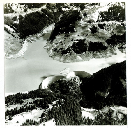 [Riprese varie del Lago artificiale dell'Hongrin e della centrale idroelettrica in valle d'Anniviers (Svizzera); un cannone per neve artificiale in azione e una cabina della funivia presso Flaine (Francia)]